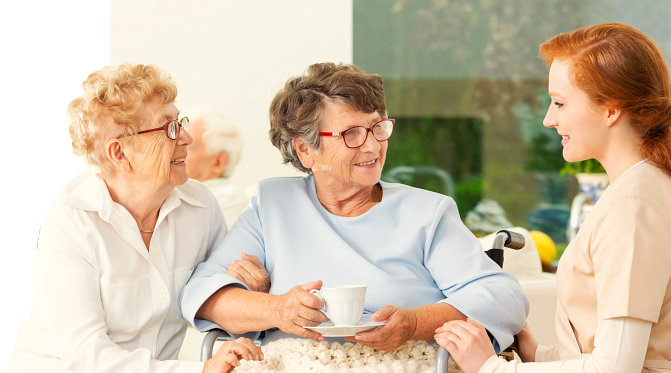 a photo of two senior women with their caregiver
