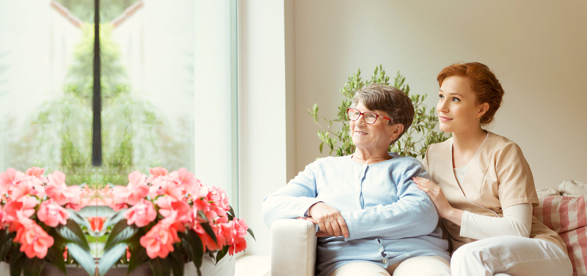 a photo of a caregiver sitting next to a senior woman
